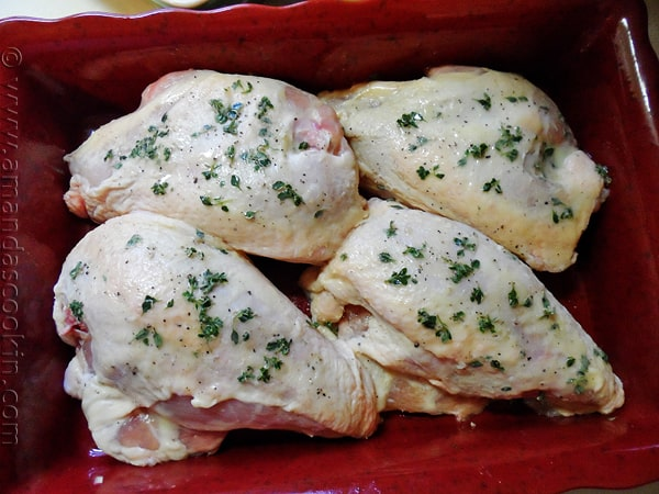 An overhead photo of chicken breasts in a red roasting pan topped with fresh lemon thyme leaves.