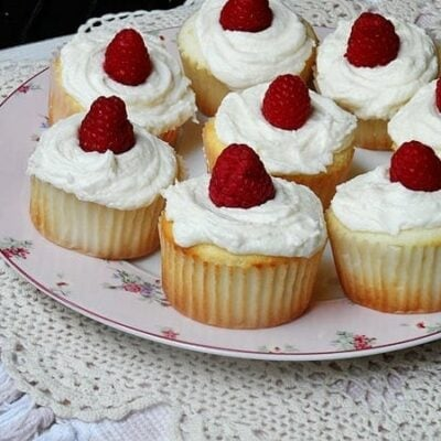A photo of a plate of raspberry filled white chocolate buttercream cupcakes.