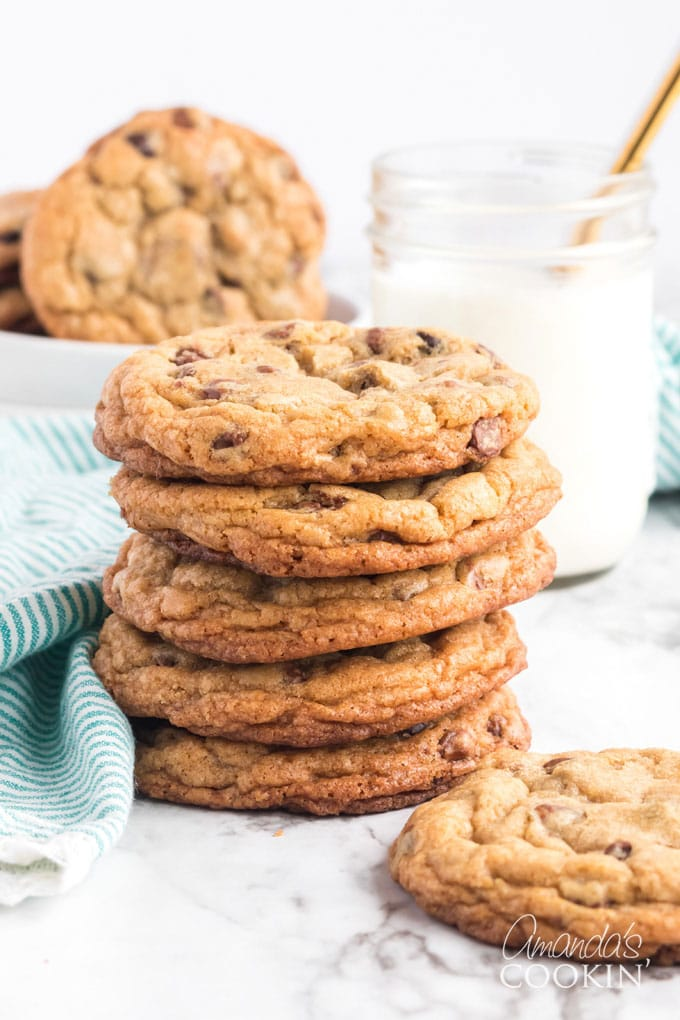 stack of chocolate chip cookies wit ha glass of milk