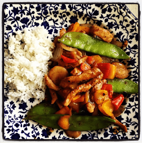 An overhead photo of a plate of peppered pork stir fry with sweet peppers with rice on the side.