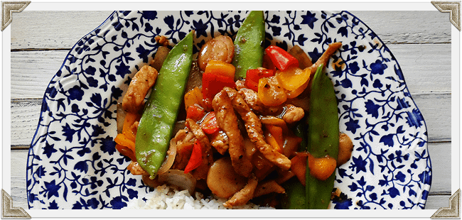 A close up photo of a plate of peppered pork stir fry with sweet peppers.