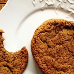 A close up photo of whole sugar topped molasses spice cookie next to a half eaten cookie on a white plate.