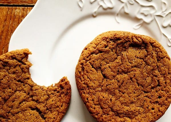 A close up photo of a whole sugar topped molasses spice cookie next to a half eaten cookie on a white plate.