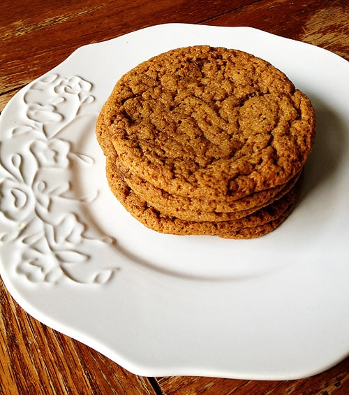 A stack of sugar topped molasses spice cookies on a white plate.