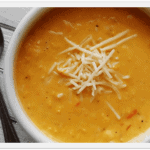 A close up photo of a bowl of creamy white cheddar corn soup.