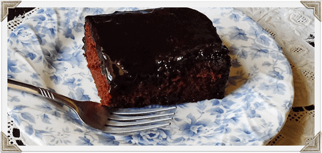 A close up photo of a serving of chocolate prune cake resting on a plate.