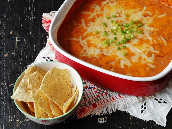 Creamy con queso bean dip in a red bowl with tortilla chips on the side.