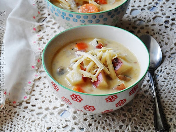 A close up photo of rustic garlic potato soup in a bowl.