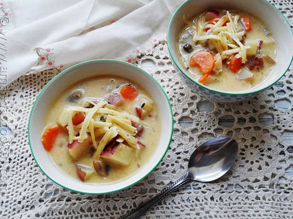 A photo of two bowls of rustic garlic potato soup.