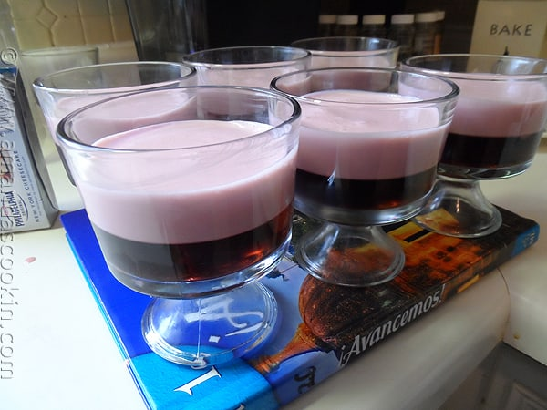A close up photo of six creamy raspberry Jell-O parfaits.