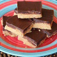 No bake peanut butter bars stacked on top of each other on a red and blue plate.