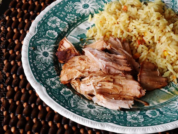 A close up photo of slow cooker oriental pork roast on a plate next to rice.