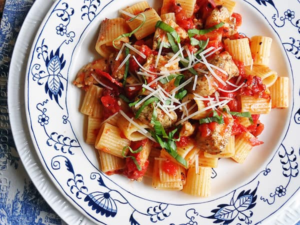 An overhead of a plate of spiced chicken and mezzi rigatoni topped with grated Parmigiano-Reggiano cheese and fresh basil.