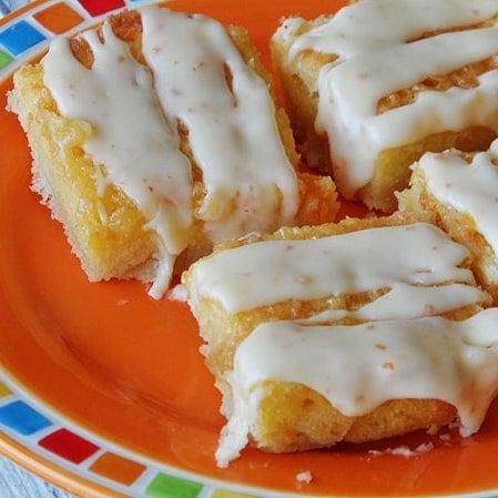 A close up photo of tropical dream dessert bars on an orange plate.