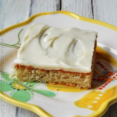 A close up photo of a banana bar with vanilla cream cheese frosting on a white plate.