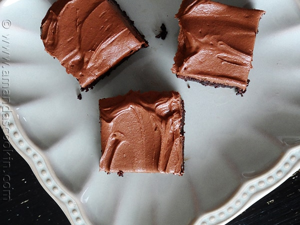 An overhead photo of fudge frosted espresso brownies on a white plate.