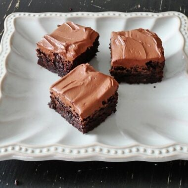 A photo of fudge frosted espresso brownies on a white platter.