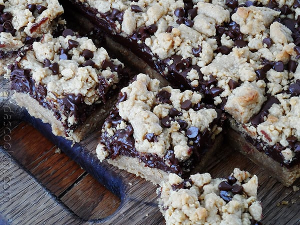 An overhead photo of peanut butter chocolate layer bars resting on a wooden cutting board.