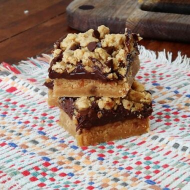 Two peanut butter chocolate layer bars stacked on top of each other.