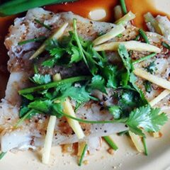 A close up photo of Chinese style parchment fish on a white plate topped with fresh cilantro.