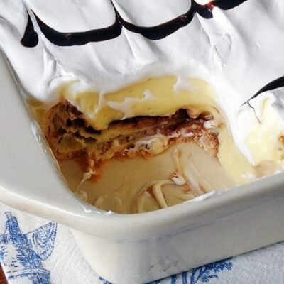 A close up photo of a cream puff chocolate eclair cake with a serving removed.