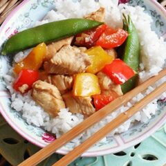 A close up photo of a bowl of kung pao chicken served over rice with chopsticks on the side.