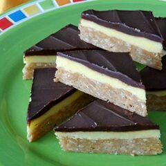 A close up photo of no bake peanut butter pudding bars resting on a green plate.