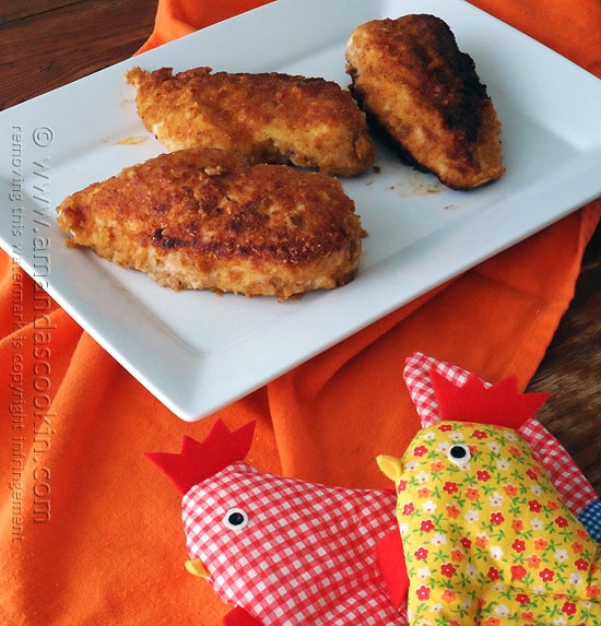 Three oven fried chicken breasts on a white plate.