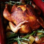A whole roasted chicken over vegetables in a roasting pan.