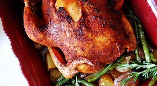 A close up photo of a whole roasted chicken over vegetables in a roasting pan.