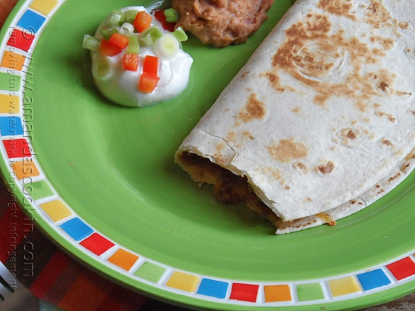 A close up photo of a beef and bean quesadilla on a green plate with sour cream and refried beans on the side.
