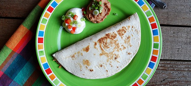 An overhead photo of a beef and bean quesadilla on a green plate with sour cream and refried beans on the side.