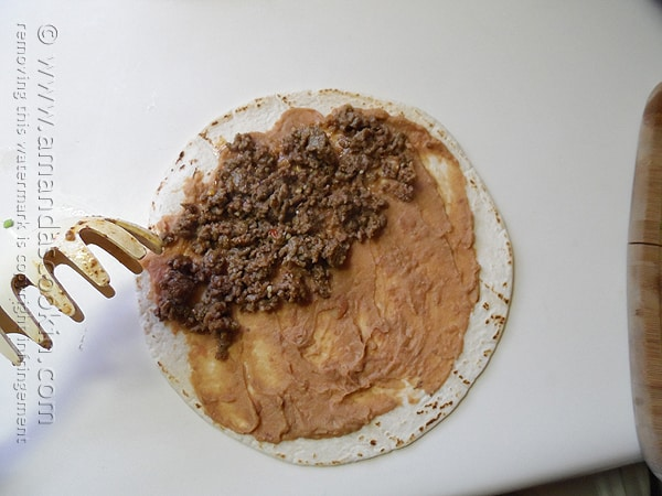 An overhead photo of a tortilla with refried beans and ground beef on top.
