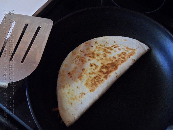An overhead photo of a beef and bean quesadilla in a skillet.