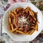 An overhead photo of penne Bolognese in a white plate with grated parmesan cheese on top.