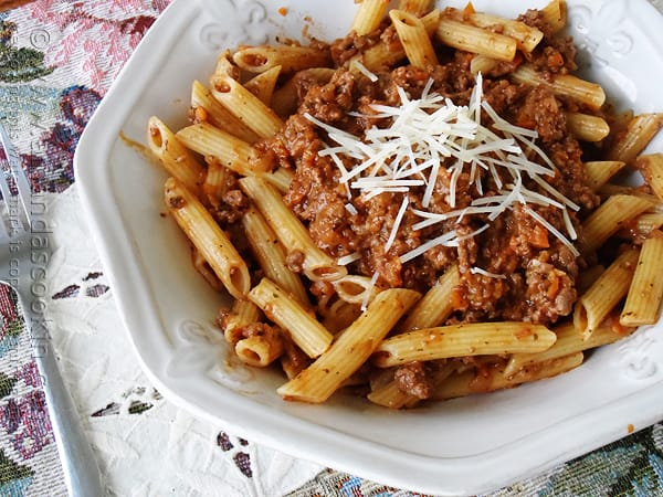 A close up photo of penne Bolognese in a white bowl with grated parmesan cheese on top.