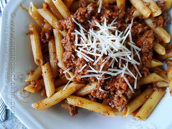 A close up overhead photo of penne Bolognese in a white bowl with grated parmesan cheese on top.