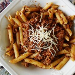 An overhead photo of penne Bolognese with grated parmesan cheese on top.