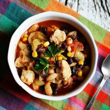 An overhead photo of a bowl of chicken chili with black beans and corn and a spoon on the side.