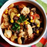 A close up overhead photo of a bowl of chicken chili with black beans and corn.
