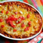 An overhead photo of a chicken tostada casserole with chopped green onions and tomatoes on top.