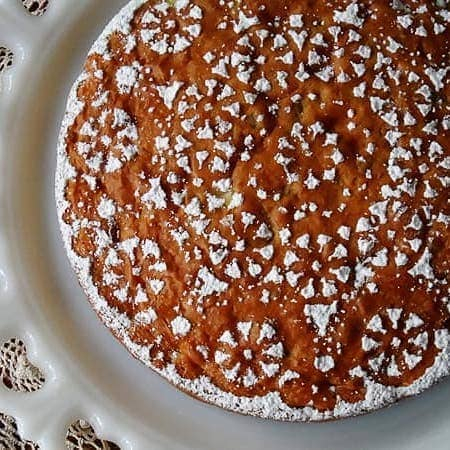 A overhead photo of a Merryfield apple cake on a decorative white platter.