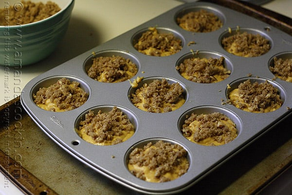 A close up photo of a muffin tin filled with pumpkin mini cake batter and cinnamon streusel topping.