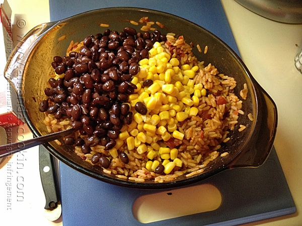 A bowl of Spanish rice with black beans and corn on top.