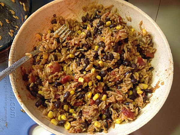 A bowl of Spanish rice with black beans and corn.