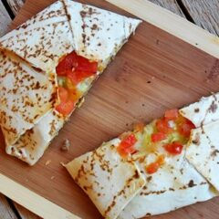 An overhead photo of a copycat crunchwrap supreme cut in half on a wooden cutting board.