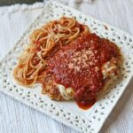 An overhead photo of chicken parmesan on a white decorative plate.