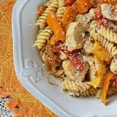 A close up overhead photo of chicken with peppers and pasta in a white bowl topped with Parmesan cheese.