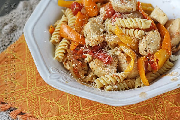 A close up photo of chicken with peppers and pasta in a white bowl topped with Parmesan cheese.