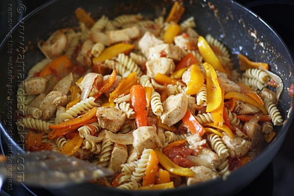 A close up photo of chicken with peppers and pasta in a skillet.